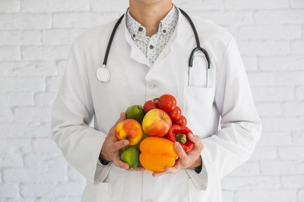 врач держит овощи и фрукты
